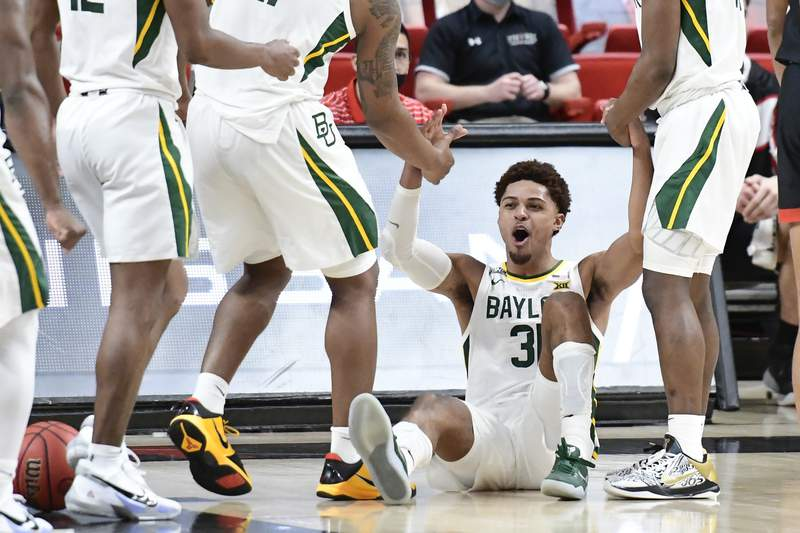 Baylor's MaCio Teague (31) is helped up by his teammates after drawing a foul against Texas Tech during the second half of an NCAA college basketball game in Lubbock, Texas, Saturday, Jan. 16, 2021. (AP Photo/Justin Rex)