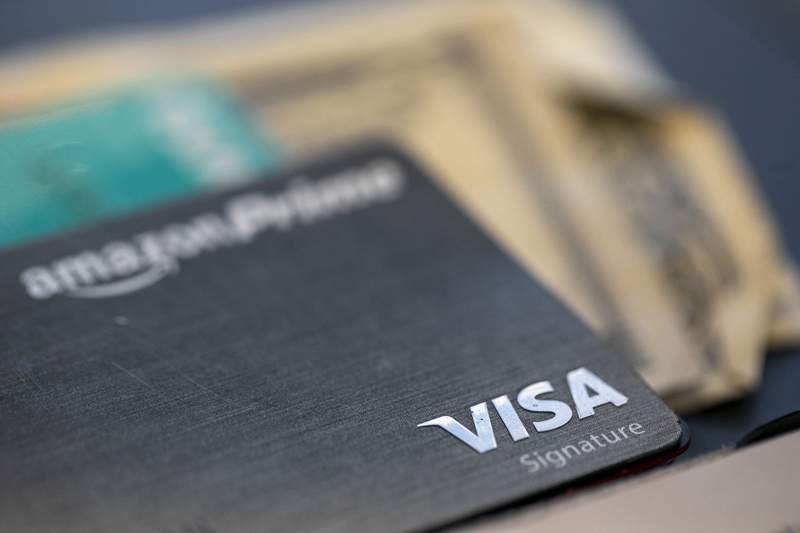 FILE - This Aug. 11, 2019, file photo shows a Visa logo on a credit card in New Orleans. Visa said Thursday, April 30, 2020, that its fiscal second-quarter profits increased 3.6% from a year earlier, helped by growth in payments being processed over the company's namesake network. (AP Photo/Jenny Kane, File)
