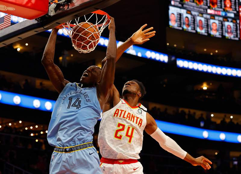 ATLANTA, GEORGIA - MARCH 02: Gorgui Dieng #14 of the Memphis Grizzlies dunks against Bruno Fernando #24 of the Atlanta Hawks in the second half at State Farm Arena on March 02, 2020 in Atlanta, Georgia.  NOTE TO USER: User expressly acknowledges and agrees that, by downloading and/or using this photograph, user is consenting to the terms and conditions of the Getty Images License Agreement.  (Photo by Kevin C. Cox/Getty Images)
