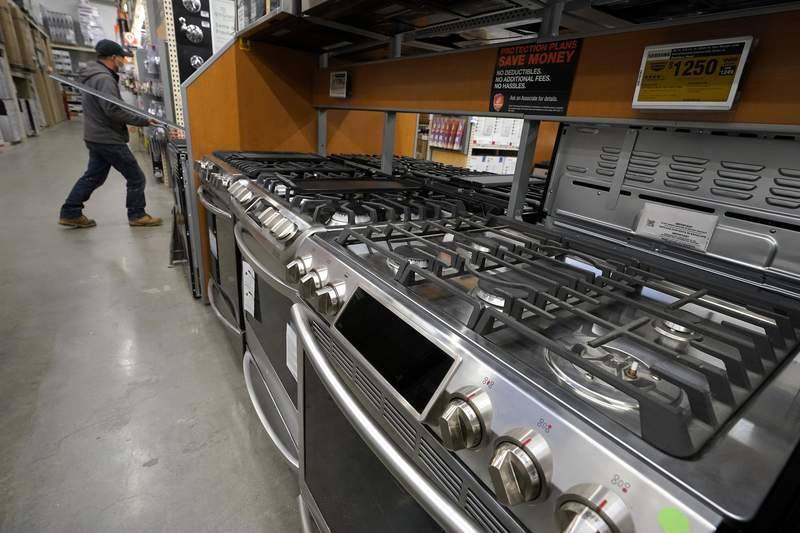 In this Oct. 29, 2020 file photo, a passer-by walks past stoves on display at a Home Depot location, in Boston. The Commerce Department reported Wednesday, March 24, 2021, that orders for durable goods declined last month for the first time after nine consecutive monthly gains including a sizable 3.5% rise in January.(AP Photo/Steven Senne)