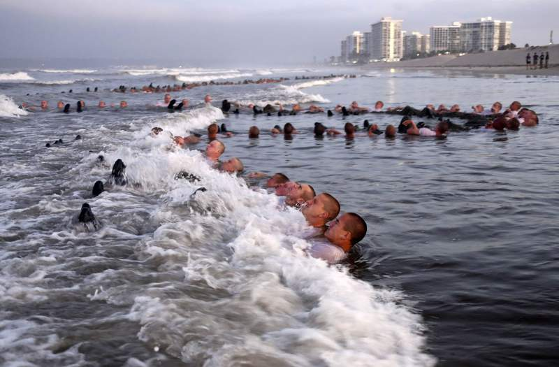 """FILE - This May 4, 2020, photo provided by the U.S. Navy shows SEAL candidates participating in """"surf immersion"""" during Basic Underwater Demolition/SEAL (BUD/S) training at the Naval Special Warfare (NSW) Center in Coronado, Calif. U.S. Navy SEALs are undergoing a major transition to improve leadership and expand their commando capabilities. (MC1 Anthony Walker/U.S. Navy via AP)"""