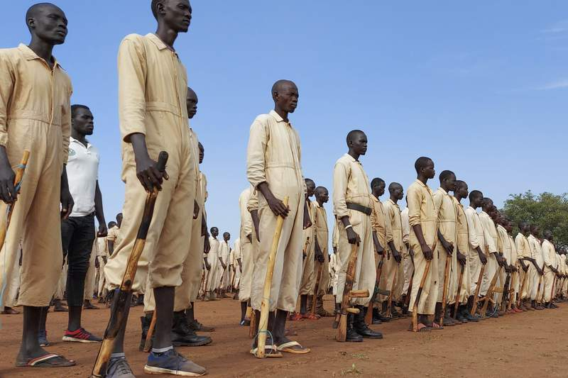 """FILE - In this Saturday, June 27, 2020 file photo, trainees parade with the wooden mock guns which they use to train with, during the visit of the defense minister to a military training center in Owiny Ki-Bul, Eastern Equatoria, South Sudan. The scale of violence in South Sudan is """"a lot worse"""" than during the country's five-year civil war, a United Nations commission announced Friday, Feb. 19, 2021, accusing senior officials of supporting armed groups that at times have included tens of thousands of fighters. (AP Photo/Maura Ajak, File)"""