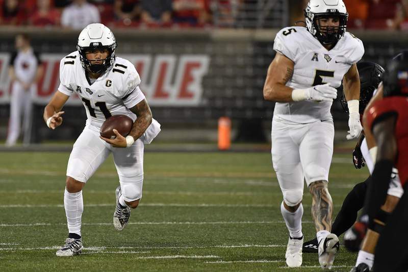 Central Florida quarterback Dillon Gabriel (11) runs through an opening in the Louisville defensive line during the first half of an NCAA college football game in Louisville, Ky., Friday, Sept. 17, 2021. (AP Photo/Timothy D. Easley)