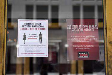 Signs posted on the door of Ruth's Chris Steak House in Austin outline the restaurant's social distancing guidelines on Wednesday, June 10. Allie Goulding/Texas Tribune