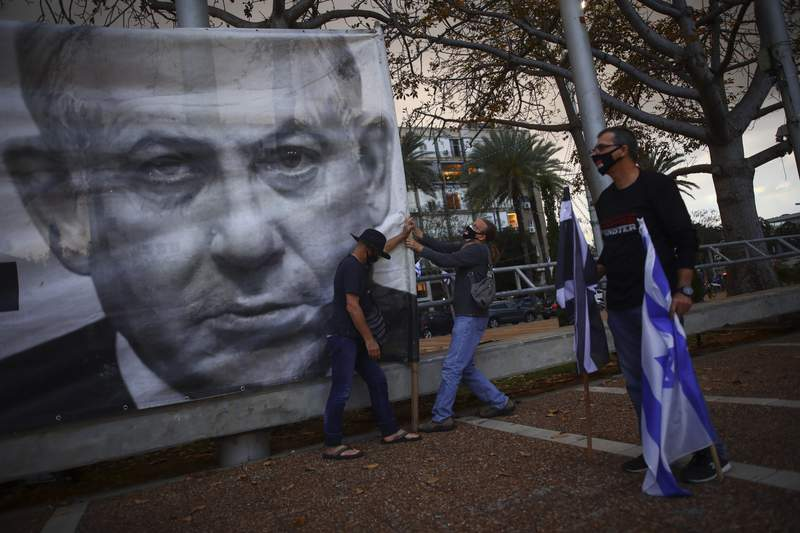 """FILE - In this April 25, 2020 file photo, demonstrators wearing protective face masks amid concerns over the country's coronavirus outbreak, hang a banner showing Israeli Prime Minister Benjamin Netanyahu during """"Black Flag"""" protest against Netanyahu and government corruption, at Rabin Square in Tel Aviv, Israel. After entering the record books last year as Israels longest-serving prime minister, Benjamin Netanyahu will once again make history on Sunday, May 24, 2020 when he becomes the countrys first sitting leader ever to go on trial.  (AP Photo/Oded Balilty, File)"""