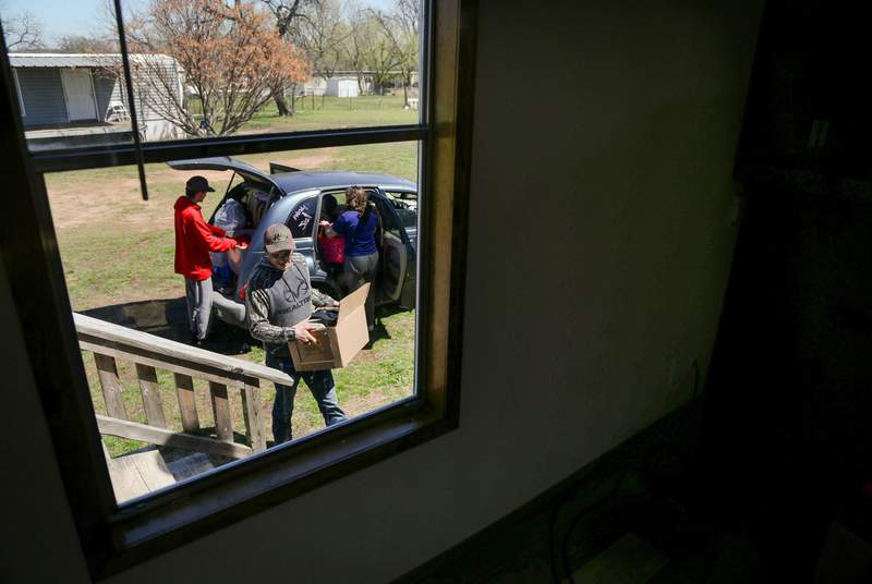 Josh Short moves a box of belongings into their new mobile home while Peyton Sidex and Amanda Garrison unpack the family car in Del Leon, on March 25, 2021.