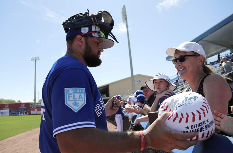 """FILE - Toronto Blue Jays' Rowdy Tellez signs autographs for fans before a spring training baseball game against the Philadelphia Phillies in Dunedin, Fla., in this Thursday, Feb. 28, 2019, file photo. The Toronto Blue Jays will play their first two homestands of the season at their spring training facility in Dunedin, Florida, because of Canadian government restrictions during the pandemic. The team said Thursday, Feb. 18, 2021, it has been planning different scenarios for home games and had hoped to see improvements in public health.  The Blue Jays cited the ongoing Canada-U.S. border closure in making the difficult decision."""" (AP Photo/Lynne Sladky, File)"""
