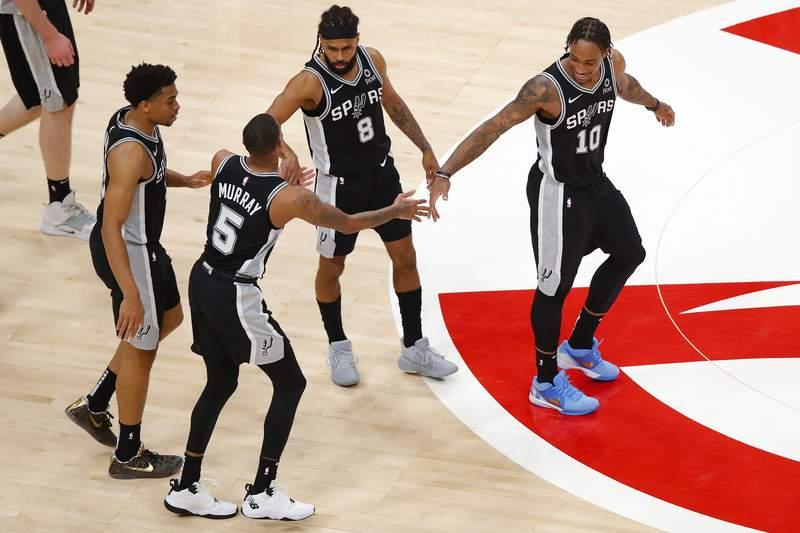 San Antonio Spurs forward Keldon Johnson, guard Dejounte Murray (5), guard Patty Mills (8) and forward DeMar DeRozan (10) react during a timeout in play during the second half of an NBA basketball game against the Atlanta Hawks on Friday, Feb. 12, 2021, in Atlanta. (AP Photo/Todd Kirkland)