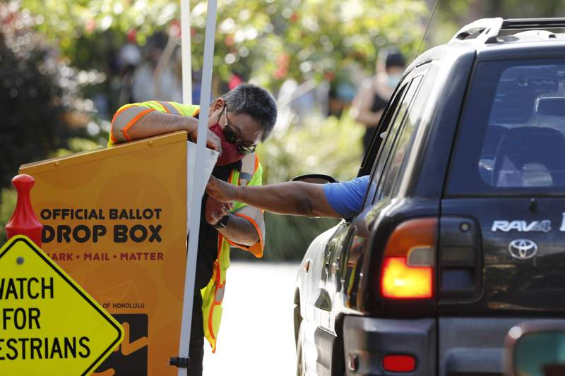 FILE - In this Nov. 3, 2020, file photo, an attendant helps a driver drop off a ballot on Election Day in Honolulu. The Hawaii Supreme Court dismissed an elections complaint challenging the entirety of the Nov. 3, general election in the islands, clearing the way for the results of the state's presidential vote to be certified. (AP Photo/Marco Garcia, File)