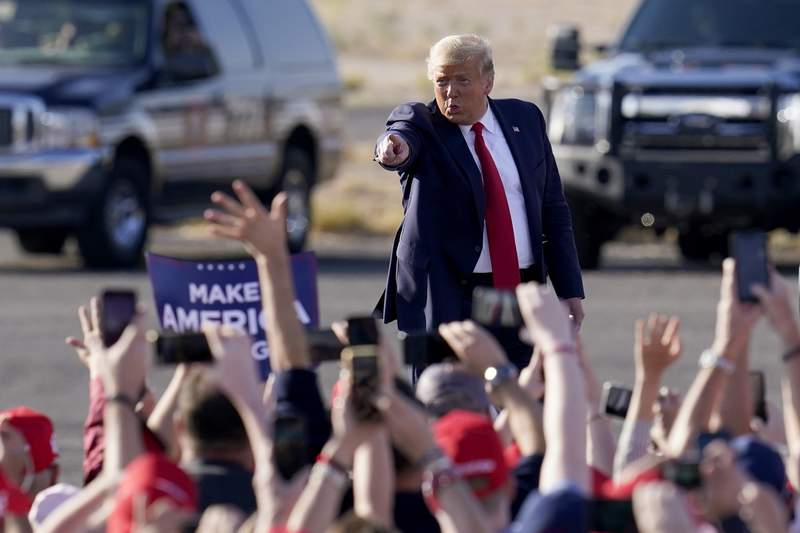 President Donald Trump waves to a cheering crowd as he arrives for a campaign rally Monday, Oct. 19, 2020, in Tucson, Ariz. (AP Photo/Ross D. Franklin)