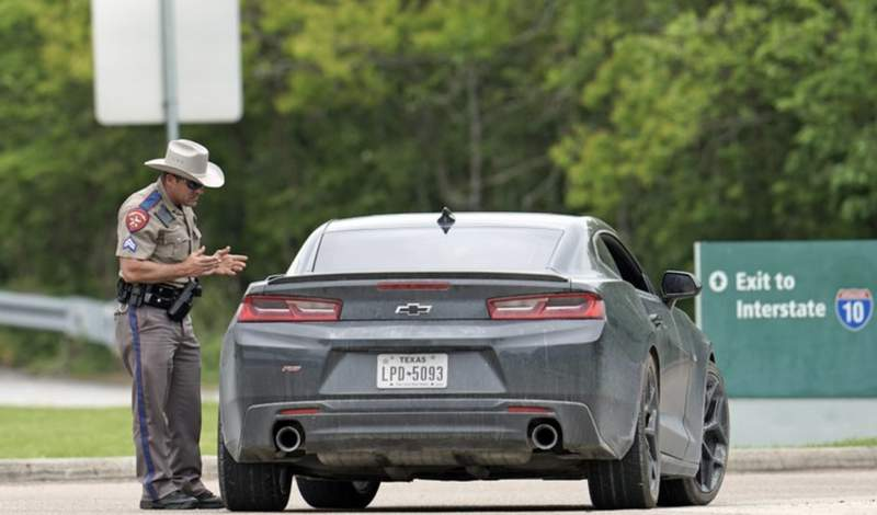 A Texas Department of Public Safety State Trooper talks with a driver at a rest stop along Interstate, 10 Monday, March 30, 2020, in Orange, Texas, near the Louisiana state border. Texas is ratcheting up restrictions on neighboring Louisiana, one of the growing hot spots for coronavirus in the U.S. Just two days after Texas began requiring airline passengers from New Orleans to comply with a two-week quarantine, Texas Gov. Greg Abbott said state troopers will now also patrol highway entry points at the Louisiana border. (AP Photo/David J. Phillip)