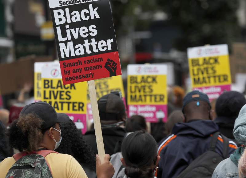 "FILE - In this Sunday, Aug. 30, 2020 file photo, Black Lives Matter protesters hold posters as they march through Notting Hill during the ""Million People March"" through central London. A body of experts that advises the United Nations on human rights concerns has slammed a widely criticized British government-backed report that concluded there was no systemic racism in the country. The U.N. Working Group of Experts on People of African Descent said Monday April 19, 2021 that it found it stunning that the report repackages racist tropes and stereotypes into fact and urged the British government to reject its findings. (AP Photo/Frank Augstein, File)"