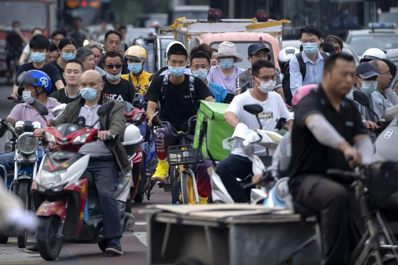 FILE - In this file photo dated Friday, July 2, 2021, people riding bicycles and scooters wait to cross an intersection during rush hour in Beijing.  China has failed to submit fresh targets for cutting their greenhouse gas emissions, UN climate change officials said Saturday July 31, 2021, among some dozens that failed provide an update on their plans by the July 31 deadline. (AP Photo/Mark Schiefelbein, FILE)