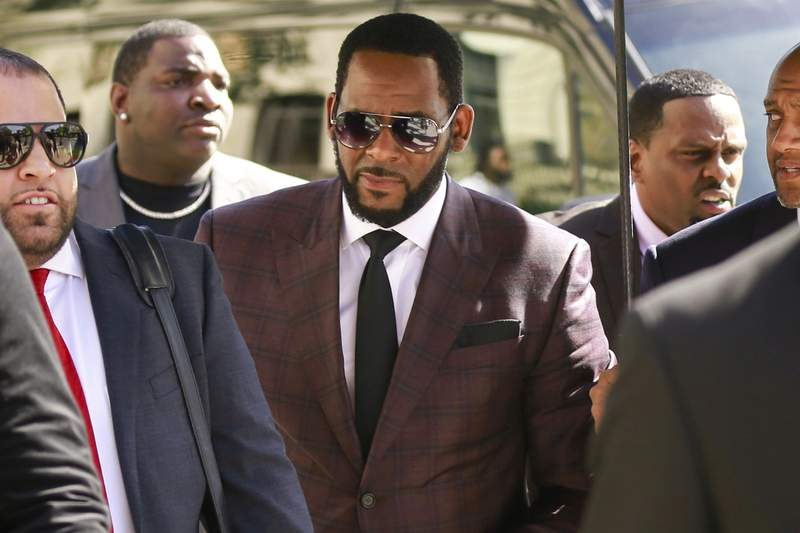 FILE - In this June 26, 2019 file photo, R&B singer R. Kelly, center, arrives at the Leighton Criminal Court building for an arraignment on sex-related felonies in Chicago. Federal prosecutors announced charges Wednesday, Aug. 12, 2020, against three men accused of threatening and intimidating women who have accused Kelly of abuse, including one man suspected of setting fire to a vehicle in Florida.  (AP Photo/Amr Alfiky, File)