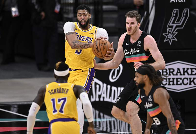Los Angeles Lakers' Anthony Davis, left rear, looks to pass to teammate Dennis Schroeder (17) as he is defended by San Antonio Spurs' Patty Mills (8) and Jakob Poeltl during the first half of an NBA basketball game, Friday, Jan. 1, 2021, in San Antonio. (AP Photo/Darren Abate)
