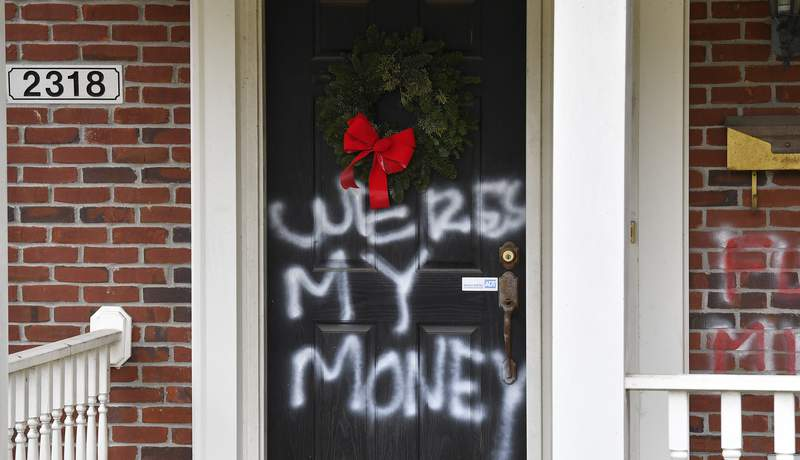 """Graffiti reading, """"Where's my money"""" is seen on a door of the home of Senate Majority Leader Mitch McConnell, R-Ky., in Louisville, Ky., on Saturday, Jan. 2, 2021. As of Saturday morning, messages like wheres my money and other expletives were written with spray paint across the front door and bricks of the Kentucky Republicans Highlands residence.    (AP Photo/Timothy D. Easley)"""