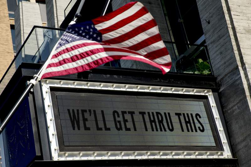 """In this April 6, 2020 photo, a sign at The Anthem music venue reads """"We'll Get Thru This"""" at the wharf which is almost completely empty because of the coronavirus outbreak in Washington. The coronavirus pandemic has gut-punched global markets, put 6.6 million Americans out of work and raised the strong likelihood of a recession. But in the Washington lobbying world, business is booming.  (AP Photo/Andrew Harnik)"""