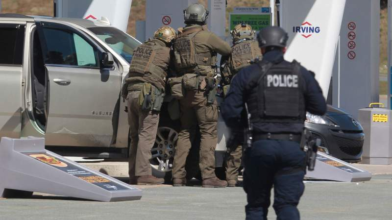 Royal Canadian Mounted Police officers prepare to take a suspect into custody at a gas station in Enfield, Nova Scotia on Sunday April 19, 2020. Canadian police  arrested a suspect in an active shooter investigation after earlier saying he may have been driving a vehicle resembling a police car and wearing a police uniform.  (Tim Krochak/The Canadian Press via AP)