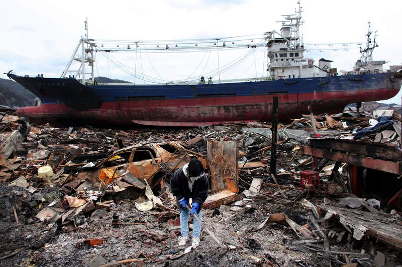 FILE - Akiko Hatareyama digs mud out of what is left of her house in front of a grounded ship on March 21, 2011 in Kesennuma, Japan. The 9.0 magnitude strong earthquake struck offshore on March 11 at 2:46pm local time, triggering a tsunami wave of up to ten metres which engulfed large parts of north-eastern Japan. (Photo by Chris McGrath/Getty Images)