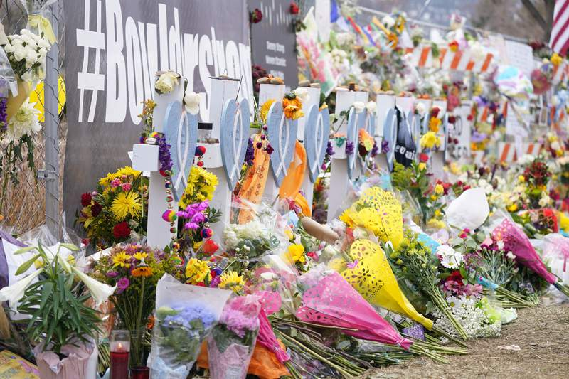 Bouquets are stack up in front of crosses put up for victims along the temporary fence line outside the parking lot of a King Soopers grocery store, the site of a mass shooting in which 10 people died, Friday, March 26, 2021, in Boulder, Colo. (AP Photo/David Zalubowski)