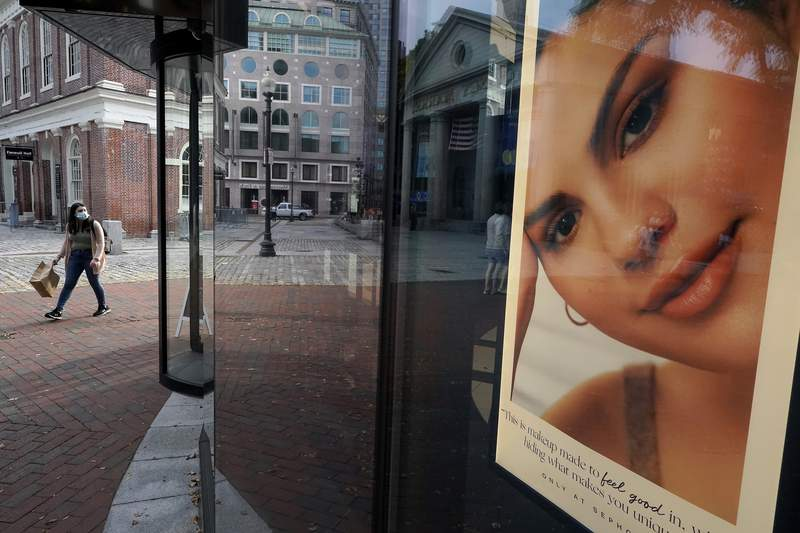 FILE - A woman carries a shopping bag while walking past a cosmetics store, right, near Faneuil Hall, behind left, Monday, Sept. 28, 2020, in Boston. The U.S. economy expanded at a 33.4% annual pace from July through September, the Commerce Department said Tuesday, Dec. 22, 2020 delivering the last of three estimates on the economys third-quarter performance.  (AP Photo/Steven Senne, file)