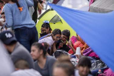 Migrants camp at the base of Paso del Norte International Bridge in Ciudad Juárez. (Ivan Pierre Aguirre for The Texas Tribune)