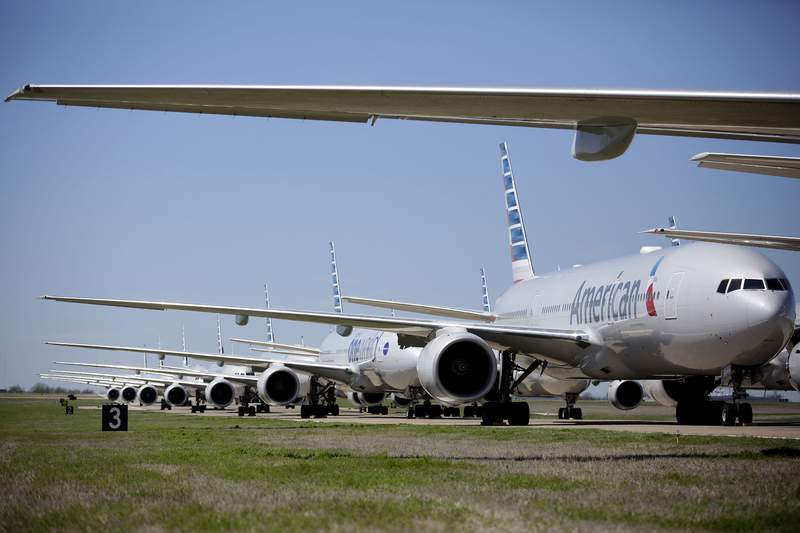 American Airlines 777's airplanes are parked at Tulsa International Airport Wednesday, March 25, 2020. American Airlines has 44 out of service airplanes parked at the airport due to a reduced flight schedule because of the COVID-19 coronavirus pandemic. (Mike Simons/Tulsa World via AP)