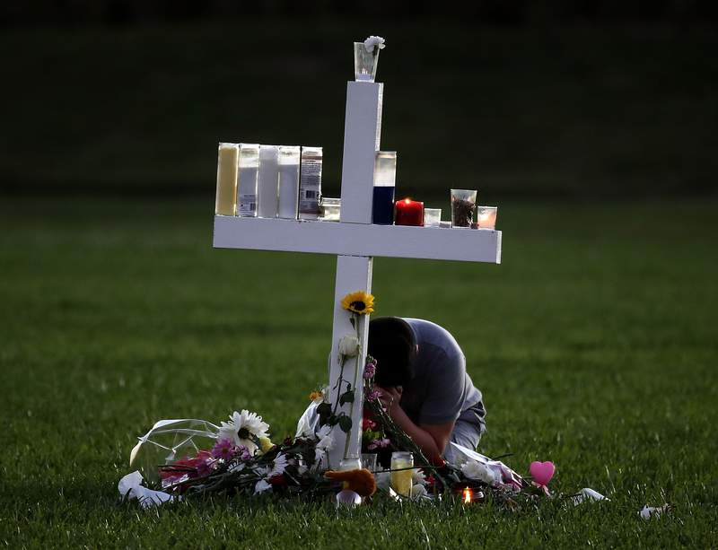 A young boy sits at a memorial honoring victims of the mass shooting at Marjory Stoneman Douglas High School, at Pine Trail Park on Feb. 16, 2018 in Parkland, Florida.