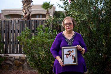 Arlinda Valencia, 68, holds a photograph taken in 1918 of her great-grandfather Longino Flores, left, great-grandmother Juana Bonilla Flores and aunt Rosa Flores Mesa. (Credit: Joel Angel Juarez for The Texas Tribune)