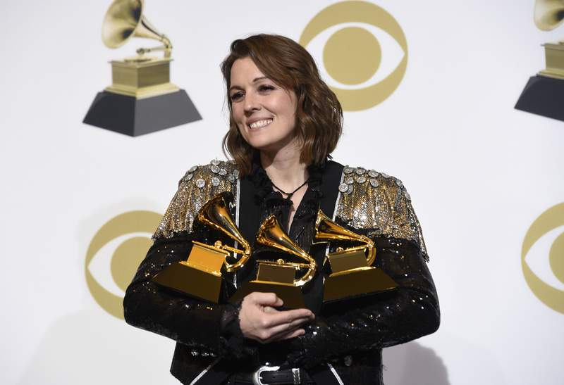 """FILE - Brandi Carlile, winner of the awards for best Americana album for """"By The Way, I Forgive You"""", best American roots performance for """"The Joke"""", and best American roots song for """"The Joke"""" poses in the press room at the 61st annual Grammy Awards in Los Angeles on Feb. 10, 2019. Carlile's memoir, """"Broken Horses"""" is coming in April. Her publisher is calling the book an evocative and piercingly honest journey through the life that has shaped her very raw art. Carlile will also read the audio edition. (Photo by Chris Pizzello/Invision/AP, File)"""
