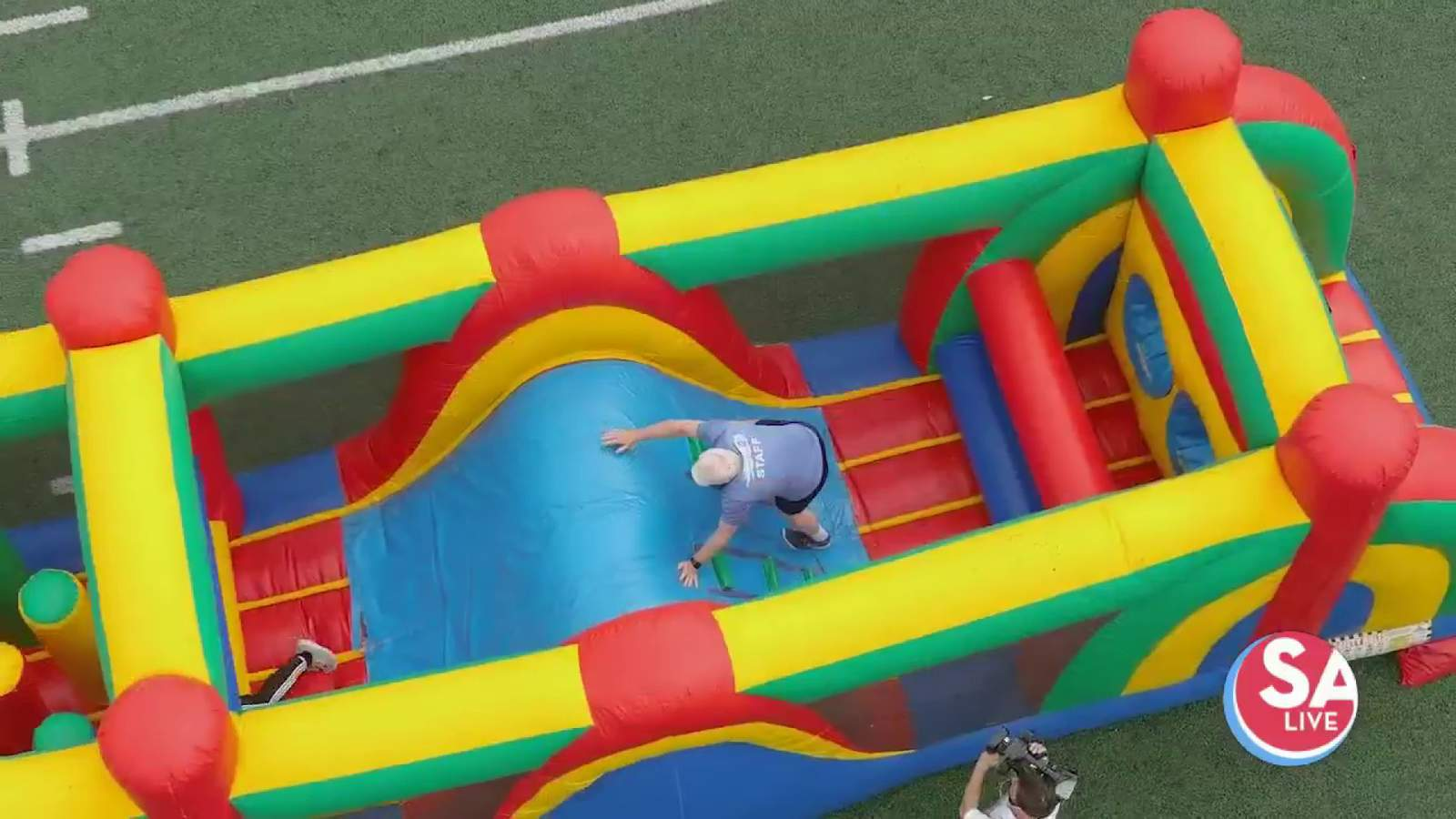 Fiona + Mike take on football-field-sized inflatable obstacle course