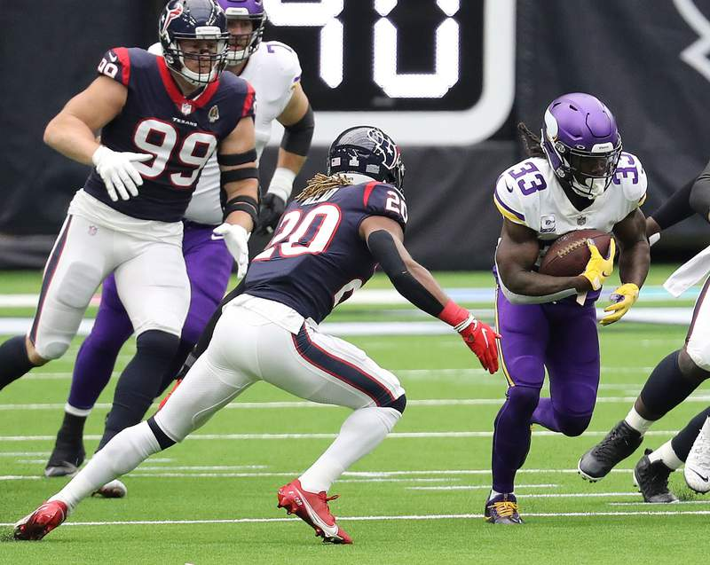 HOUSTON, TEXAS - OCTOBER 04: Dalvin Cook #33 of the Minnesota Vikings rushes past Justin Reid #20 of the Houston Texans and J.J. Watt #99 during the first quarter at NRG Stadium on October 04, 2020 in Houston, Texas. (Photo by Bob Levey/Getty Images)