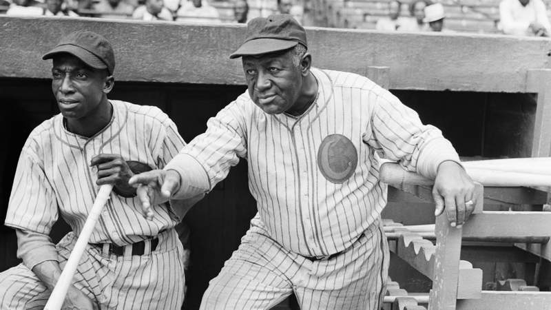 """Hall of Famer James """"Cool Papa"""" Bell (left) and manager Jim Taylor stand on the dugout steps during a Chicago American Giants game."""