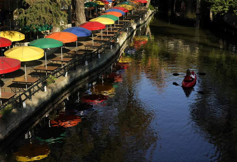 A kayaker paddles along the River Walk, Friday, Dec. 4, 2020, in downtown San Antonio. A program that has allowed kayaking on the business portion of the River Walk has been extended through January. (AP Photo/Eric Gay)