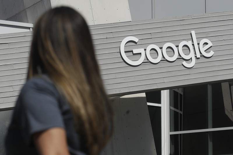 FILE - In this Sept. 24, 2019, file photo, a woman walks below a Google sign on the campus in Mountain View, Calif. In results announced Tuesday, Feb. 2, 2021, Googles digital advertising empire is regaining the momentum it lost during the pandemics early stages. And its YouTube video service is maturing into a major marketing magnet and companies are anticipating more spending by cooped-up consumers when the economy reopens. (AP Photo/Jeff Chiu, File)