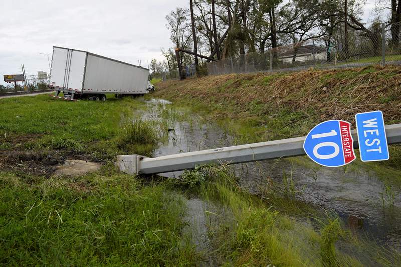 A truck and Interstate 10 sign is seen on Thursday, Aug. 27, 2020, in Lake Charles, La., after Hurricane Laura moved through the state. (AP Photo/Gerald Herbert)
