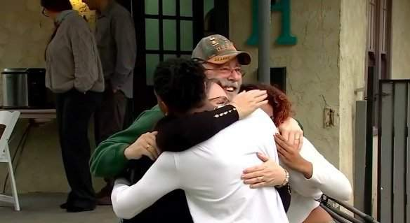 The Denches hug Jamal and his girlfriend Mikaela.