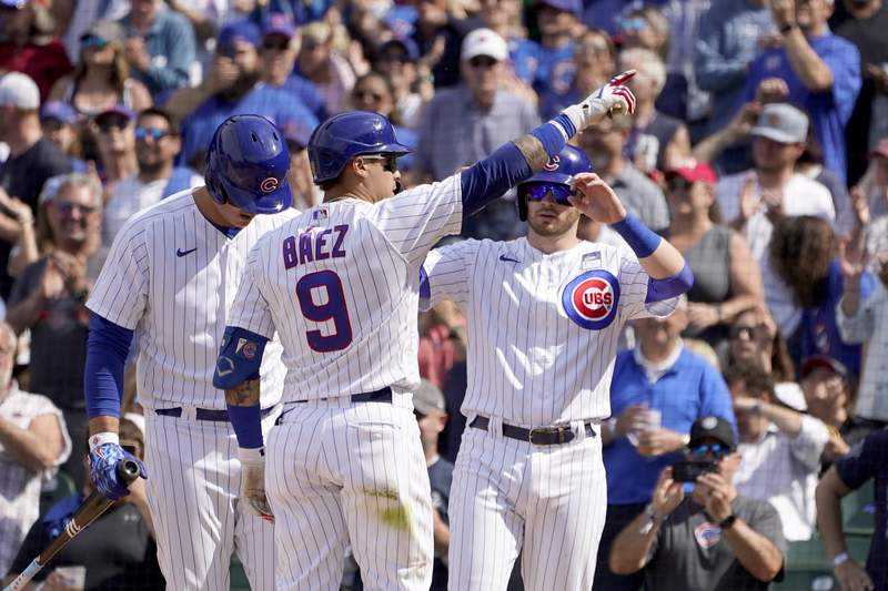 Chicago Cubs' Javier Baez (9) points to the fans as he celebrates his two-run home run off San Diego Padres relief pitcher Miguel Diaz with Anthony Rizzo, left, and Ian Happ in the seventh inning of a baseball game Wednesday, June 2, 2021, in Chicago. (AP Photo/Charles Rex Arbogast)