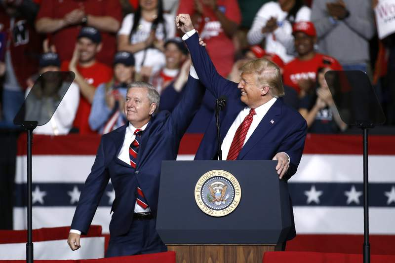 FILE - In this Feb. 28, 2020 file photo, Sen. Lindsey Graham, R-S.C., left, stands onstage with President Donald Trump during a campaign rally, in North Charleston, S.C. Jaime Harrison has raised more money than his Republican opponent, Sen. Lindsey Graham, two quarters in a row. (AP Photo/Patrick Semansky, File)