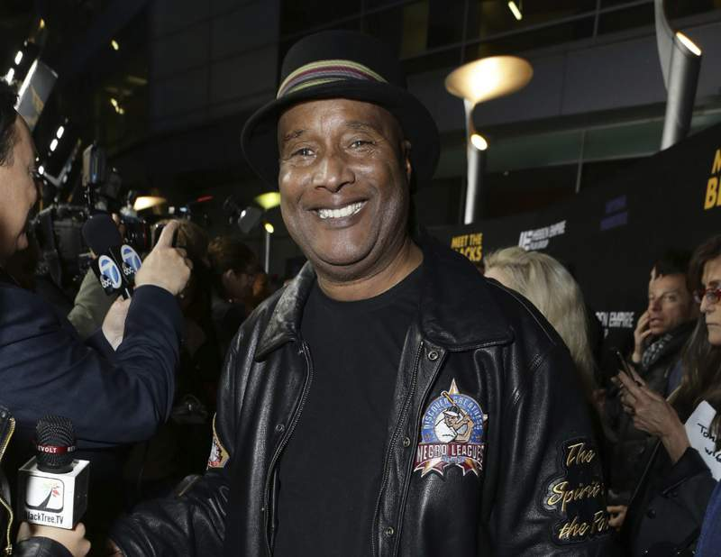 """This March 29, 2016 image released by Meet The Blacks, LLC shows Paul Mooney posing at the premiere of """"Meet the Blacks"""" in Los Angeles. Mooney, a boundary-pushing comedian who was Richard Pryors longtime writing partner and whose sage, incisive musings on racism and American life made him a revered figure in stand-up, died of a heart attack at his Oakland, Calif. home on Wednesday. He was 79.(Eric Charbonneau/Meet The Blacks via AP)"""