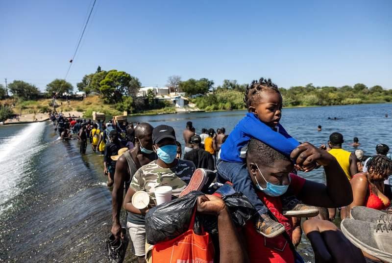 Migrants cross the Rio Grande between Del Rio and Ciudad Acua to bring supplies back to a temporary migrant camp under the international bridge in Del Rio on Sept. 17, 2021.