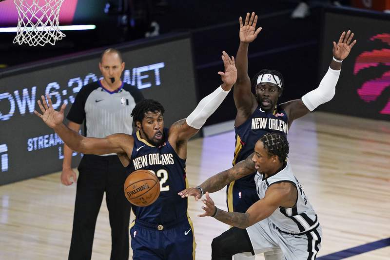 San Antonio Spurs' DeMar DeRozan, front right, passes the ball past New Orleans Pelicans center Derrick Favors, left, and guard Jrue Holiday, back, dunring the second half of an NBA basketball game, Sunday, Aug. 9, 2020, in Lake Buena Vista, Fla. (AP Photo/Ashley Landis, Pool)