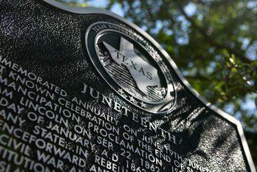 The Juneteenth historic marker is located on Strand Street in Galveston. The marker commemorates June 19, 1865, the day that Union soldiers arrived in Galveston to inform enslaved black Texans that slavery had ended, two and a half years after President Lincoln's Emancipation Proclamation. June 15, 2020. (Pu Ying Huang for The Texas Tribune)