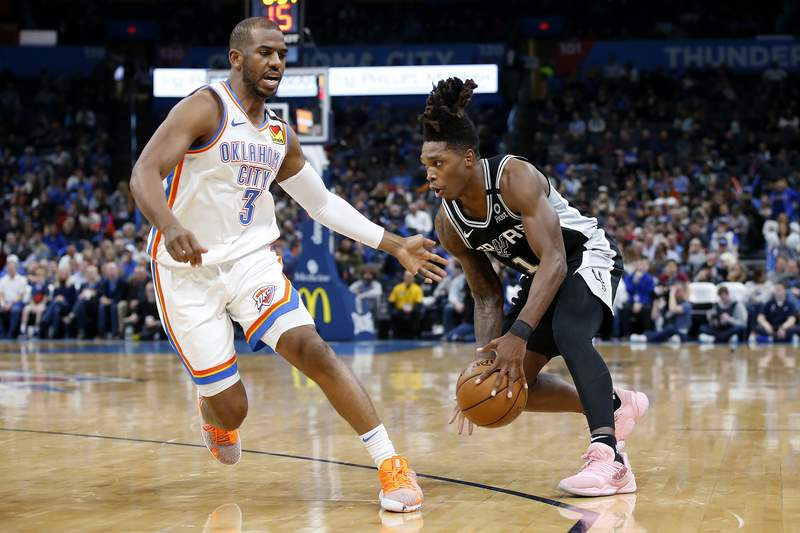 San Antonio Spurs' Lonnie Walker IV (1) goes against Oklahoma City Thunder's Chris Paul (3) during the second half of an NBA basketball game in Oklahoma City, Tuesday, Feb. 11, 2020. (AP Photo/Garett Fisbeck)