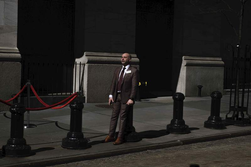 A market trader takes a break outside of the New York Stock Exchange on Monday, March 9, 2020, in New York. Stocks went into a steep slide Monday on Wall Street as coronavirus fears and a crash in oil prices spread alarm through the market, triggering the first automatic trading halt in over two decades. (AP Photo/Yuki Iwamura)
