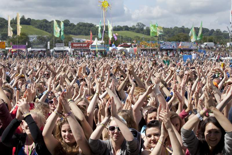 FILE - In this Friday, June 24, 2011 file photo, the crowd at Glastonbury Music Festival clap their hands above their heads as they watch Chipmunk on stage, Glastonbury, England. Britains Glastonbury music festival has fallen victim to the coronavirus pandemic for the second year in a row, organizers Michael Eavis and Emily Eavis said Thursday Jan. 21, 2021. (AP Photo/Joel Ryan, File)