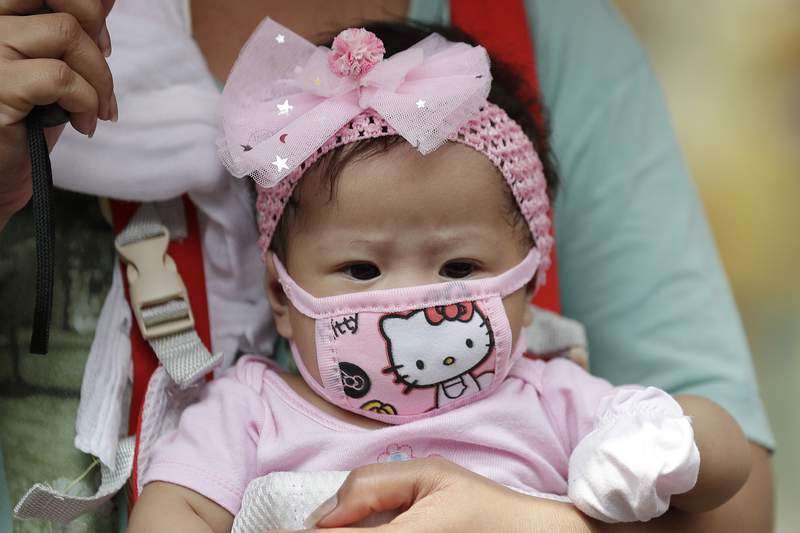 A baby wears a protective mask in Manila, Philippines on Wednesday, March 11, 2020. For most people, the new coronavirus causes only mild or moderate symptoms, such as fever and cough. For some, especially older adults and people with existing health problems, it can cause more severe illness, including pneumonia. (AP Photo/Aaron Favila)
