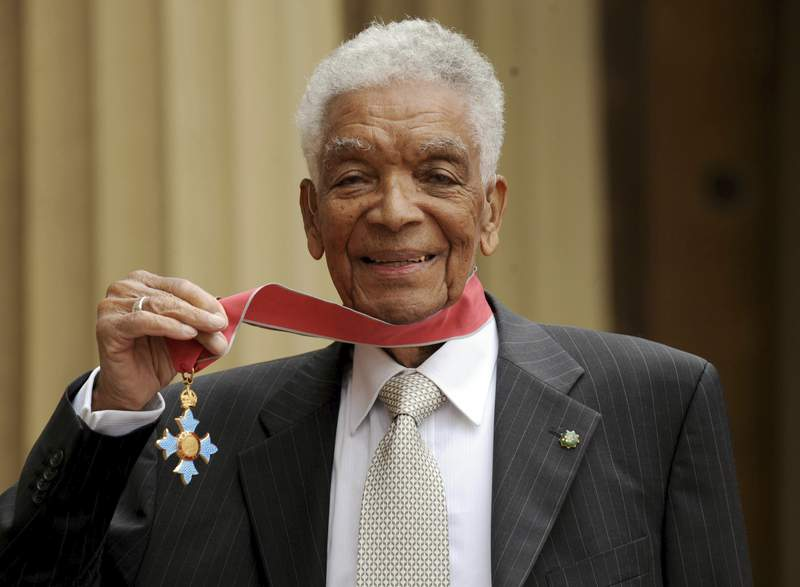FILE - In this May 28, 2009 file photo, Earl Cameron poses for the media outside Buckingham Palace after being presented his CBE by Prince Charles, in London. Bermudian acting legend Earl Cameron has died, aged 102, it was announced Saturday, July 4, 2020. He was appointed a Commander of the Most Excellent Order of the British Empire in 2009 for his accomplishments, which included being the first black actor to star in a British feature film. (Anthony Devlin/PA via AP, file)