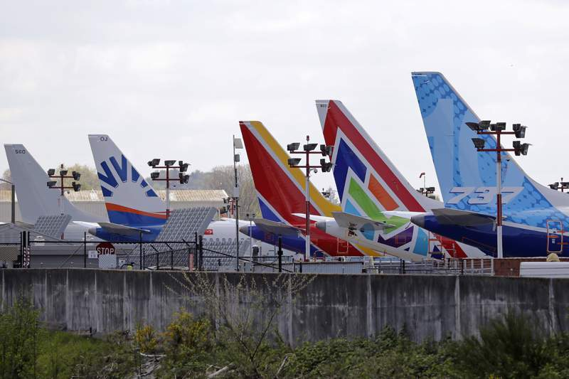 FILE - In this April 20, 2020, file photo, a line of Boeing 737 MAX jets sit parked on the airfield adjacent to a Boeing production plant in Renton, Wash. Boeing Co. has said it will outsource a significant amount of information technology work to Dell starting in April 2021, including support of cloud services, databases and information technology. The Seattle Times reported that Susan Doniz, vice president for information technology and data analytics for Boeing, told employees Thursday, Feb. 4 that the eliminated jobs represent about 10% of the company's IT staff. (AP Photo/Elaine Thompson, File)