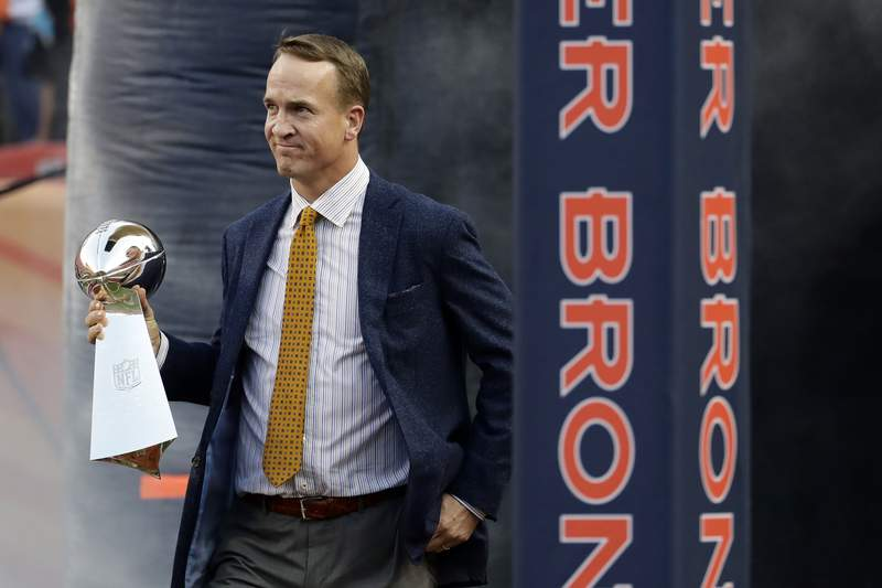 FILE - Former Denver Broncos quarterback Peyton Manning carries the Vince Lombardi Trophy from Super Bowl 50 onto the field prior to an NFL football game against the Carolina Panthers in Denver, in this Thursday, Sept. 8, 2016, file photo. Manning was selected Saturday, Feb. 6, 2021, for induction into the Pro Football Hall of Fame's Class of 2021.   (AP Photo/Jack Dempsey, File)